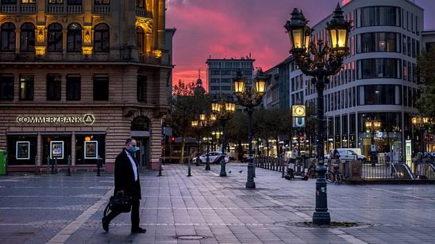 Muž s rouškou se prochází kolem budovy Opery ve Frankfurtu