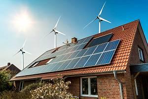 Solární panely na střeše domu a větrné turbíny - koncept udržitelných zdrojů.