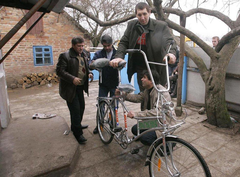 Leonid Stadnyk si prohlíží s kamarády ve vesnici Podoljanci nové jízdní kolo, vyrobené specielně pro něj.
