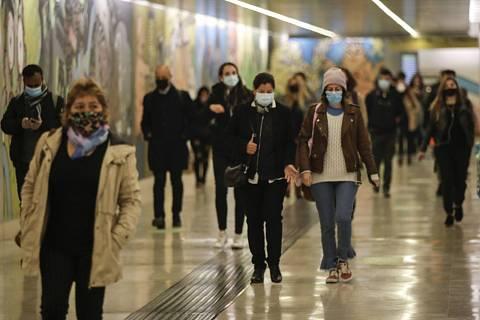 Lidé s rouškami ve stanici metra v Miláně