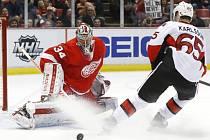 Brankář Detroitu Petr Mrázek kryje střelu Erika Karlssona z Ottawy.
