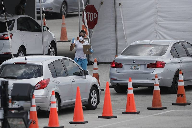 Zdravotnice v roušce se pohybuje mezi auty, která stojí ve frontě v americkém Miami Gardens. Řidiči čekají na testování na covid-19.