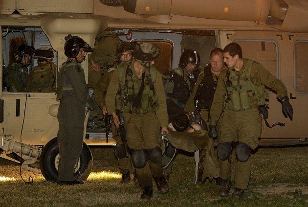 Izraelští vojáci v pásmu Gazy přenášejí zraněného spolubojovníka.