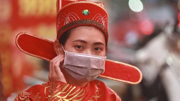 Prodavačka ve stejnokroji s rouškou na ústech ve zlatnictví ve vietnamské Hanoji