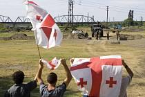 Gruzínci mávají vlajkami před kontrolním stanovištěm ruských vojáků z mírové mise před gruzínským městem Poti. Ruská armáda už Gruzii opustila, zůstává jen mírová mise podle dřívějších dohod.
