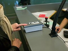 Cestující na pasové kontrole na letišti JFK V New Yorku scanuje otisk svého prstu.