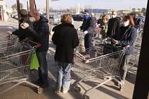 Lidé s rouškami čekají před obchodem v Casalpusterlengu na severu Itálie