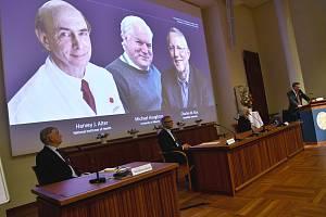 Vyhlášení Nobelovy ceny za lékařství, na obrazovce zleva ocenění vědci (zleva) Američan Harvey Alter, Brit Michael Houghton a Charles Rice z USA