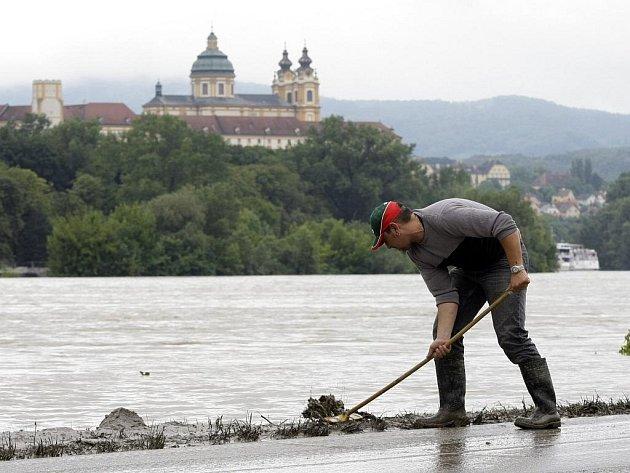 Místní obyvatel čistí od bahna silnici v rakouské vesnici Emmersdorf. V pozadí je vidět klášter v Melku.