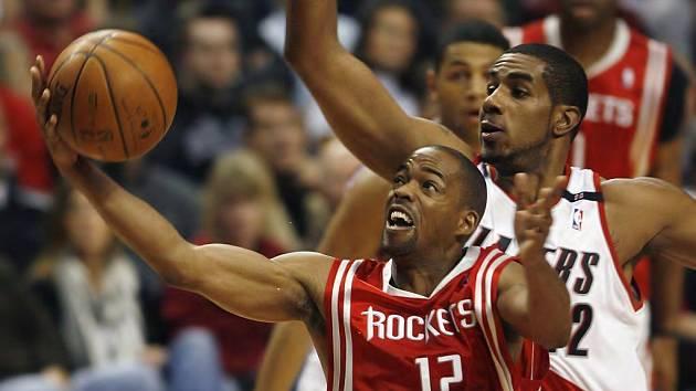 Rafer Alston z Houstonu Rockets (č. 12) se snaží zkrotit míč před dotírajícím LaMarcus Aldridgem z Portlandu Trail Blazers.