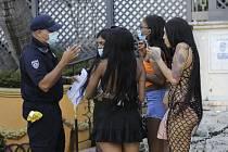 Policista mluví 24. července 2020 v Miami Beach s ženami o povinném nošení roušek.