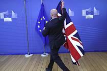 Člen protokolu připravuje vlajky EU a Británie před jednáním o brexitu. Ilustrační foto