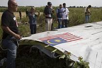 Členové vyšetřovacího týmu z Malajsie a Organizace pro bezpečnost a spolupráci v Evropě (OBSE) zkoumají trosky malajsijského letadla