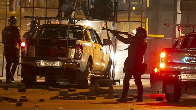 Policista se zbraní blokuje 10. srpna 2020 cestu před demonstranty v Minsku