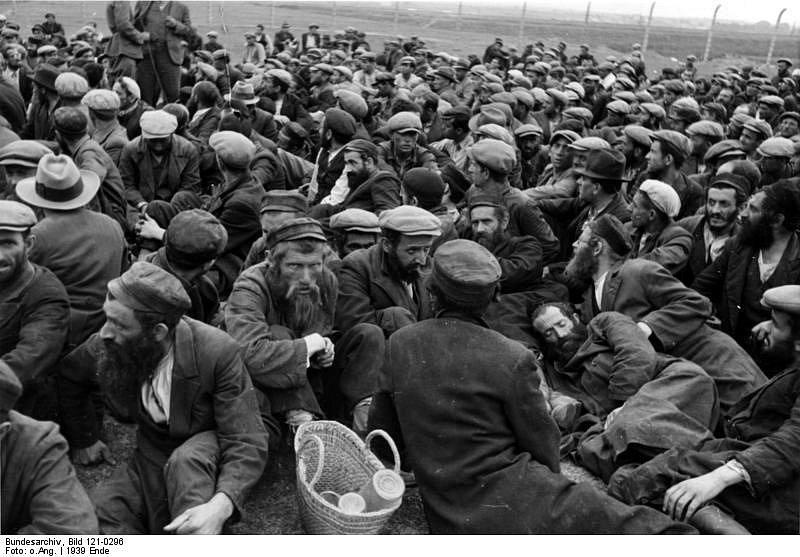 Krakovská oblast, konec roku 1939. Zajatí Židé, sehnaní na otrocké práce, sedí na otevřeném prostranství obklopeném novým plotem z ostnatého drátu