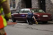 Policista prohlíží vínově červený Jaguár, který vjel v centru Helsinek do davu lidí.