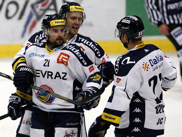 Hokejisté Vítkovic (zleva) Rudolf Huna, Tomáš Kudělka a Karol Sloboda se radují z gólu proti Slavii.