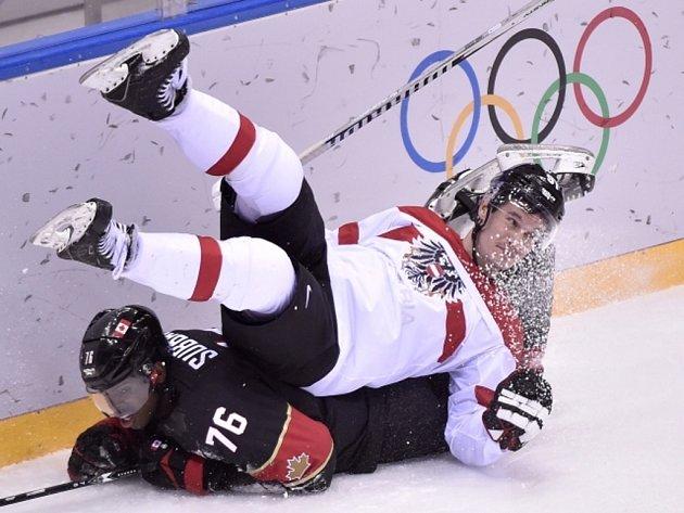 Oliver Setzinger z Rakouska padá na P.K. Subbana z Kanady na olympijských hrách v Soči.