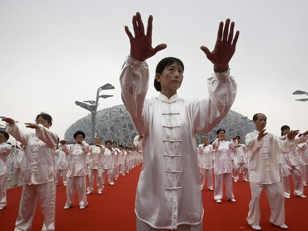 Číňané cvičící před olympijským stadionem. Uspořádá Peking po letních také zimní hry?