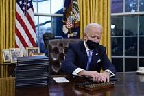Nový americký prezident Joe Biden podepisuje první dokumenty v Oválné pracovně Bílého domu.