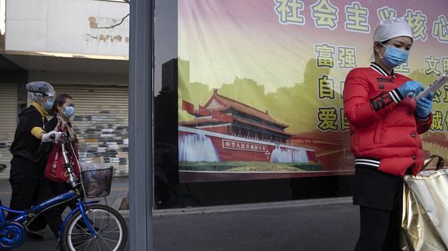 Žena v roušce stojí 13. dubna 2020 před plakátem, na kterém je zobrazena Brána nebeského klidu (Tchien-an-men)