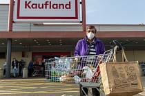 Seniorka odchází z nákupu dopoledne 19. března 2020 ze supermarketu Kaufland v Ústí nad Labem. V prodejnách potravin, drogeriích a lékárnách smějí být mezi 10:00 a 12:00 jen zákazníci starší 65 let. Nařizuje to mimořádné opatření proti šíření nového typu