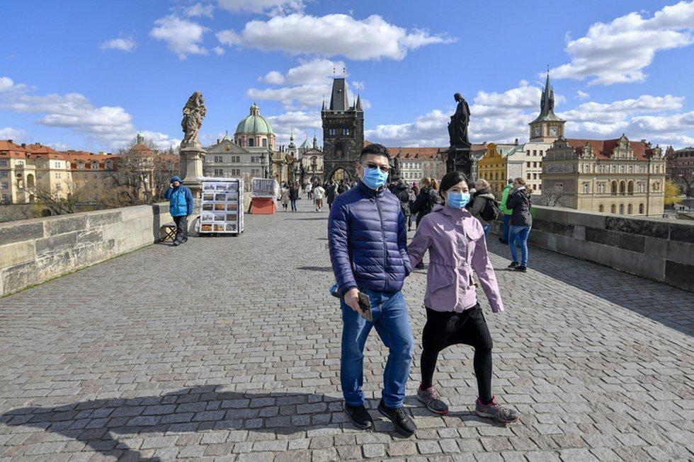 Turisté s rouškami na Karlově mostě