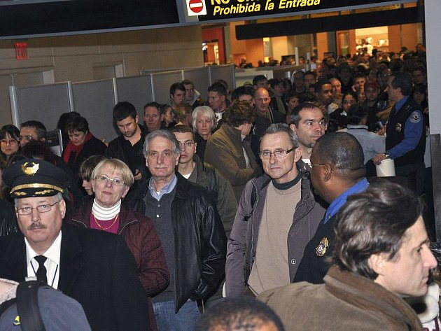 Cestující čekají na bezpečnostní kontrolu poté, co byl terminál letiště v americkém Newarku uzavřen kvůli muži, který se právě bezpečnostní prohlídce vyhnul.