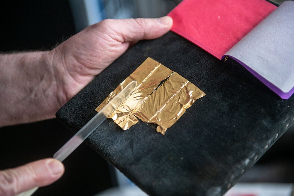 Zlaté plátky jsou tak tenké, že při práci Václav Hodinka skoro ani nedýchá. Plátky přichytí pomocí vazelíny na z štětec z veverčích chlupů. Před samotným zlacením si zlato nakrájí na kožené podložce.