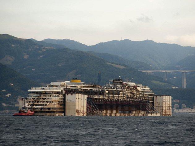 Vrak italské výletní lodě Costa Concordia dnes ráno po téměř roční přípravě dorazil na místo v janovském přístavu, kde ho dělníci sešrotují.