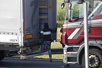 Imigranti se snaží dostat do kamionu ve francouzském přístavu Calais.