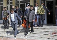 Tělo jedné z obětí je vynášeno z budovy po masakru na univerzitě v Baku.