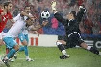 Švýcarský brankář Diego Benaglio akrobaticky zasahuje před Ardou Turanem.