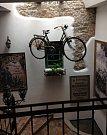 KOLO JAKO ARTEFAKT. Dámský bicykl vyrobila firma Lněnička a syn. Vpravo je fotografie velocipedistů s Antonínem Kasperem.