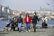 Lidé na náplavce Rašínova nábřeží v Praze za slunečného počasí