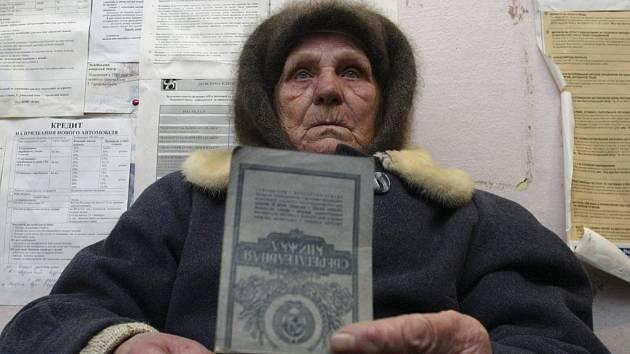 Žena čeká s připravenými doklady před bankou v Kyjevě na vyplacení kompenzace za dluh ze sovětských dob.