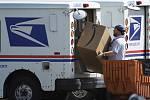 Zaměstnanec americké pošty (USPS) nakládá do automobiliu zásilku