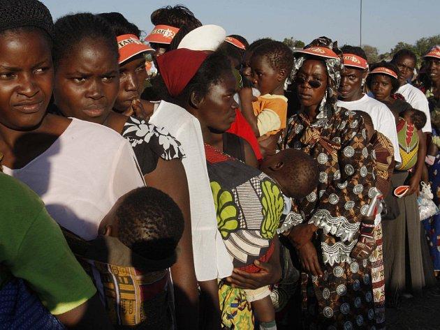 Vesničanky v zambijské vesnici čekají na sítě proti komárům, které nabízí iniciativa Roll Back Malaria.