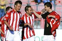 Fotbalisté Žižkova (zleva) Michal Kropík, Vladan Milosavljev a Matej Sivrič se radují z gólu.
