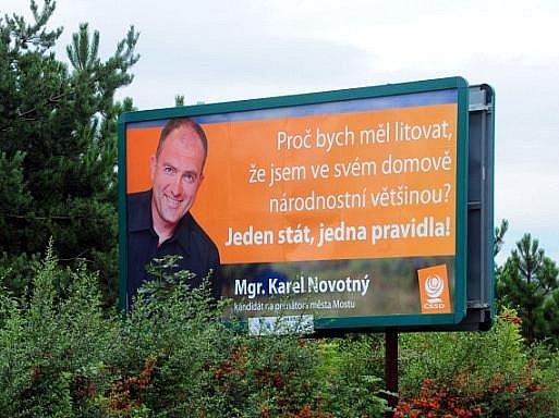 """Vedení ČSSD chce po mostecké organizaci, aby odstranila kontroverzní billboard s mosteckým lídrem Karlem Novotným. Je na něm použitý slogan: """"Proč bych měl litovat, že jsem ve svém domově národnostní většinou? Jeden stát, jedna pravidla."""""""