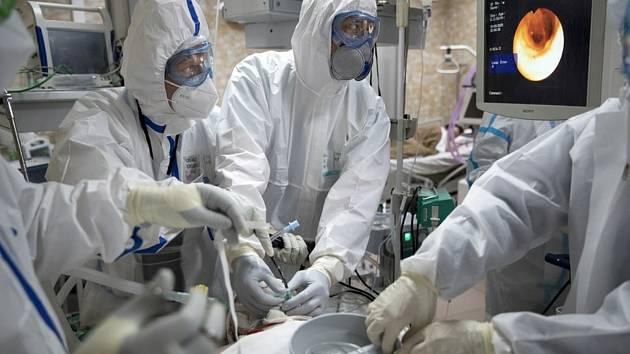 Ruští doktoři provádějí tracheální intubaci pacientovi s koronavirem na jednotce intenzivní péče v jedné z moskevských nemocnic.