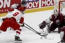 Ruský hokejista Dmitrij Orlov (vlevo) střílí na lotyšského brankáře Elvise Merzlikinše