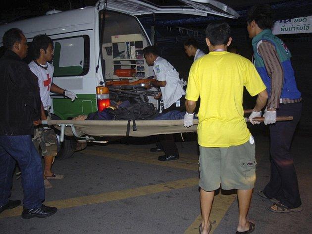 Zdravotníci nakládají demonstranta zraněného granátem do sanitky v Bangkoku.