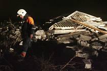 Záchranáři prohledávají budovu zničenou havarovaným Beechcraftem.