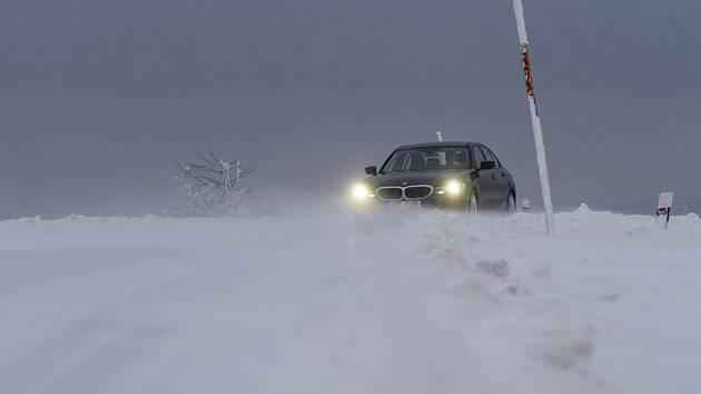 Auto na zasněžené silnici. Ilustrační foto.