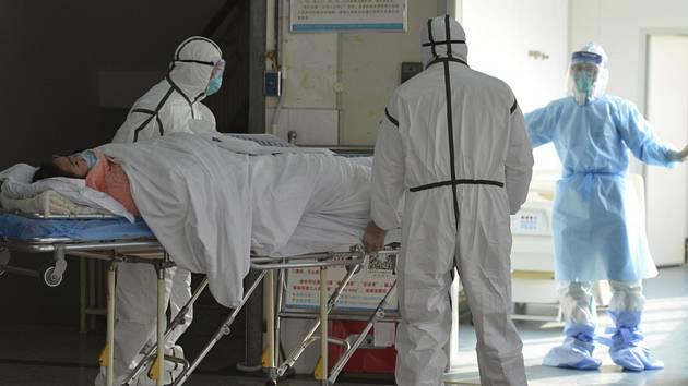 Zdravotnící v nemocnici v čínském městě Fu-jang v provincii An-chuej převáží pacienta nakaženého koronavirem na izolaci (snímek z 1. února 2020)