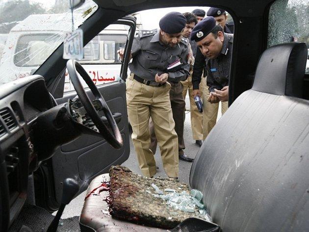 Pákistánští vyšetřovatelé prohlížejí zničený policejní mikrobus, v němž jeli ochránci srílanského kriketového mužstva.