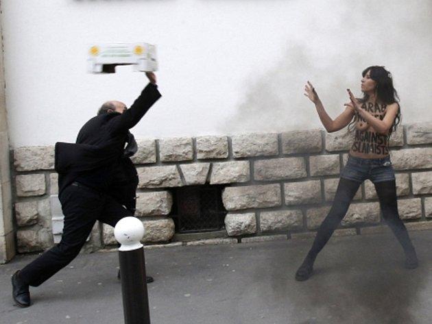Polonahá feministka z hnutí Femen u pařížské velké mešity demonstrativně spálila vlajku salafismu, což je fundamentalistická verze islámu.