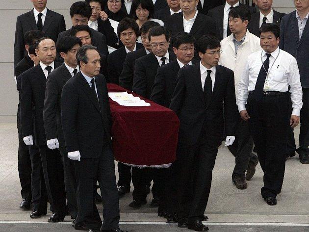 Pohřební zřízenci vynášejí rakev s ostatky exprezidenta Ro Mu-hjona.
