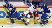 Jiří Tlustý se snaží vydolovat puk mezi švédskými hokejisty.